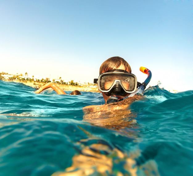 Junge schwimmt im meer, sommerferien Premium Fotos