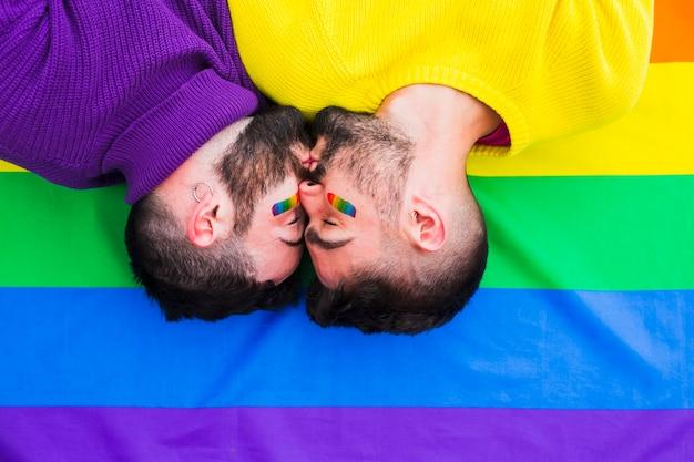 Junge schwule paare, die auf regenbogenflagge küssen
