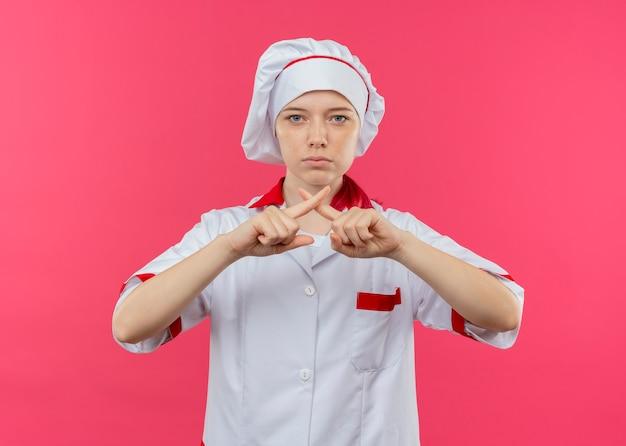 Junge selbstbewusste blonde köchin in kochuniform kreuzt fingergesten nicht isoliert auf rosa wand Kostenlose Fotos