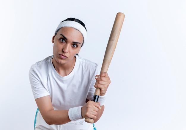 Junge selbstbewusste kaukasische sportliche frau, die stirnband und armbänder trägt, hält fledermaus, der kamera betrachtet Kostenlose Fotos