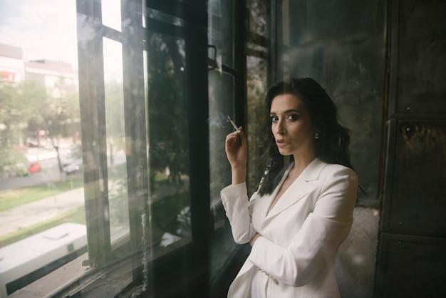 Junge sexy brunettefrau in der klage, die am fenster eine zigarette zuhause raucht Premium Fotos