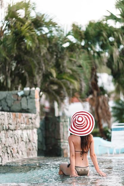 Junge sexy frau, die rest am rand des swimmingpools im freien genießt Premium Fotos