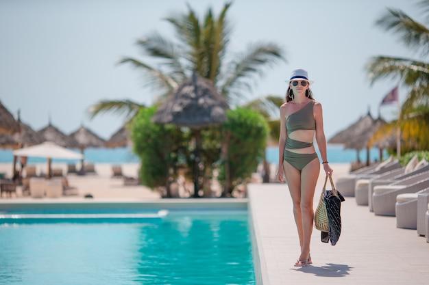 Junge sexy frau, die rest swimmingpool im im freien genießt Premium Fotos