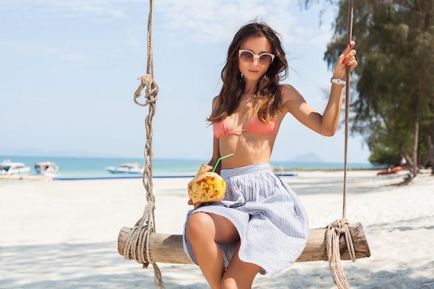 Junge sexy frau sitzt auf schaukel am tropischen strand, sommerferien, modestil, rock, bikinioberteil, trinkenden kokosnusscocktail, lächelnd, entspannend Kostenlose Fotos
