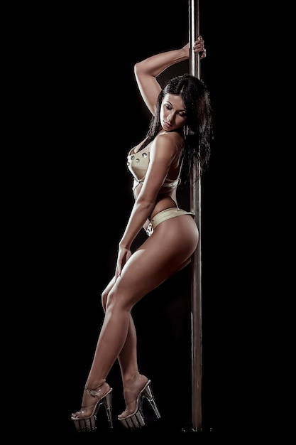 Junge sexy frau übt pole dance vor einem schwarzen hintergrund aus Kostenlose Fotos