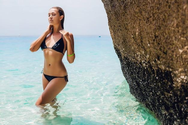 Junge sexy schlanke frau, schöner perfekter körper, gebräunte haut, schwarzer bikini-badeanzug, sonnenbaden im klaren blauen wasser ozean, sommerferien in asien, sinnlich, heiß, reisen in thailand, tropischer strand Kostenlose Fotos