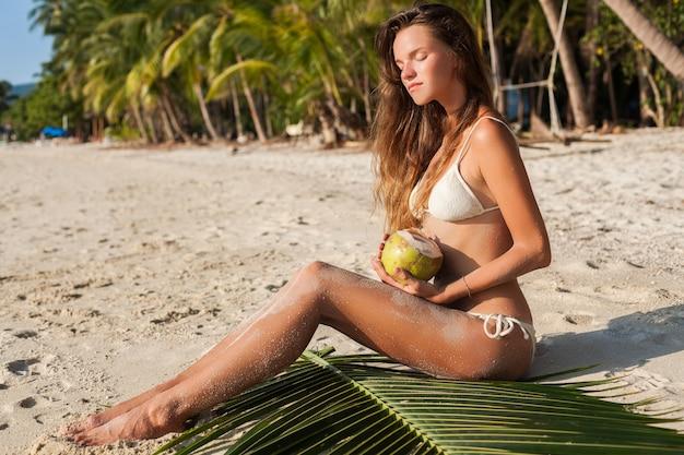 Junge sinnliche frau in der weißen bikini-badebekleidung, die kokosnuss hält, lächelnd, sonnenbad auf tropischem strand. Kostenlose Fotos