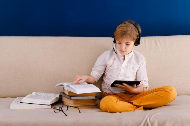 Junge sitzt auf der couch, isst popcorn und spielt mit gamepad während seiner online-lektion zu hause, soziale distanz während der quarantäne, selbstisolation, online-bildungskonzept Premium Fotos