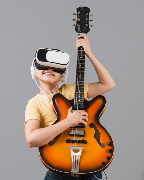 Junge spielt gitarre, während er virtual-reality-headset verwendet Kostenlose Fotos