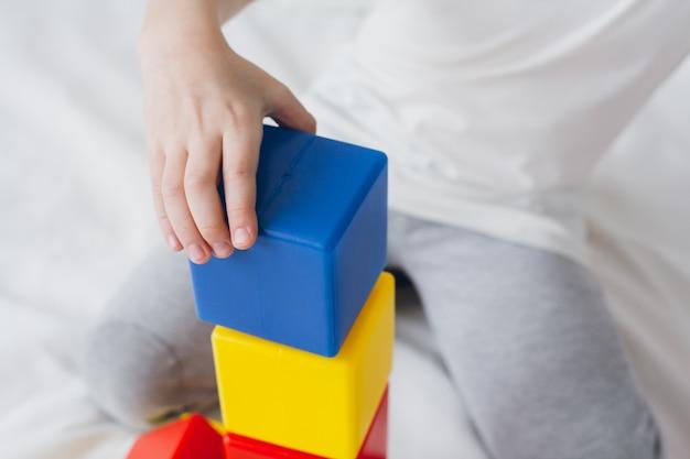 Junge spielt und baut einen turm aus bunten plastikwürfeln Premium Fotos