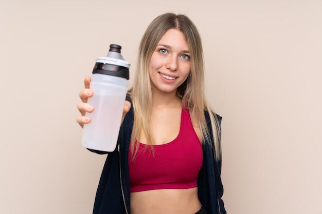 Junge sportblondine über isolierter wand mit sportwasserflasche Premium Fotos