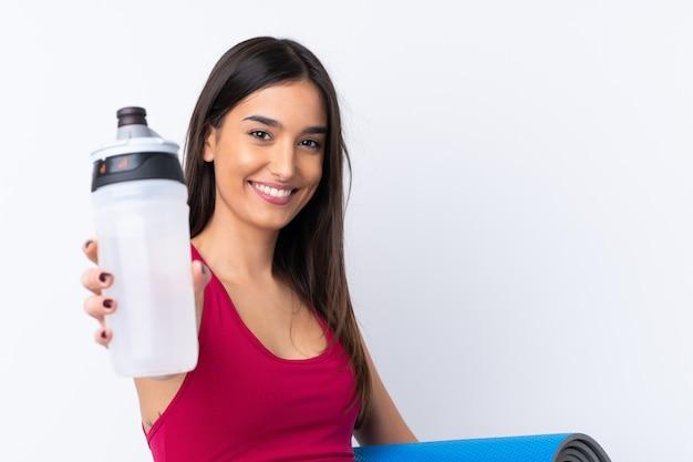 Junge sportbrünette frau über isolierte weiße wand mit sportwasserflasche und mit einer matte Premium Fotos