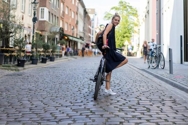 Junge sportfrau auf einem fahrrad in einer europäischen stadt. sport in urbanen umgebungen. Kostenlose Fotos