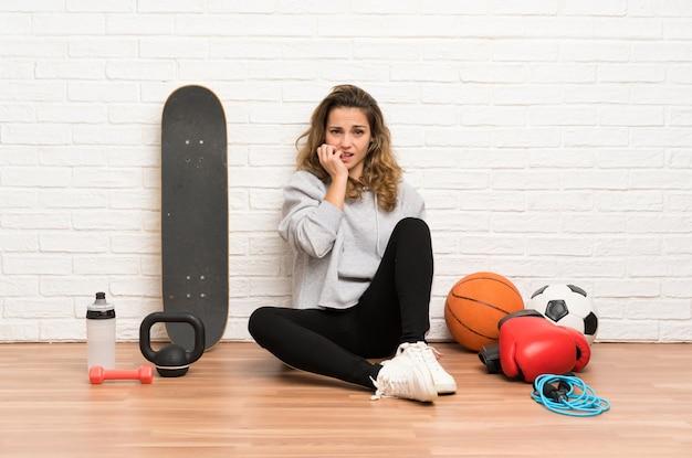Junge sportfrau, die auf dem boden nervös und erschrocken sitzt Premium Fotos