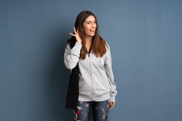 Junge sportfrau, die auf etwas hört, indem sie hand auf das ohr setzt Premium Fotos