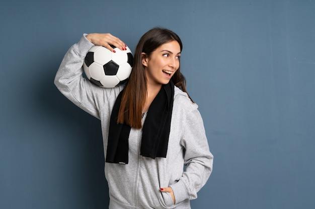 Junge sportfrau, die eine fußballkugel anhält Premium Fotos