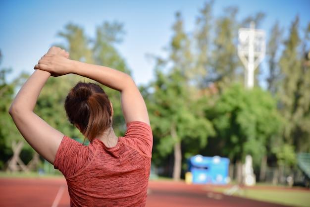 Junge sportfrau, die ihre arme auf stadionsbahn bevor dem laufen ausdehnt. Premium Fotos