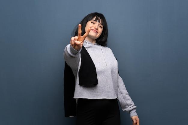 Junge sportfrau, die siegeszeichen lächelt und zeigt Premium Fotos