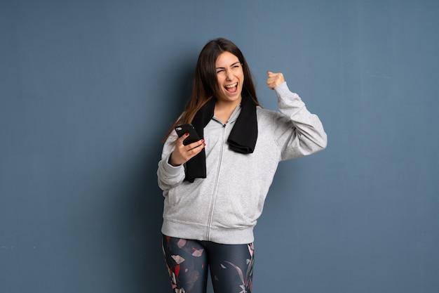 Junge sportfrau mit telefon in siegposition Premium Fotos