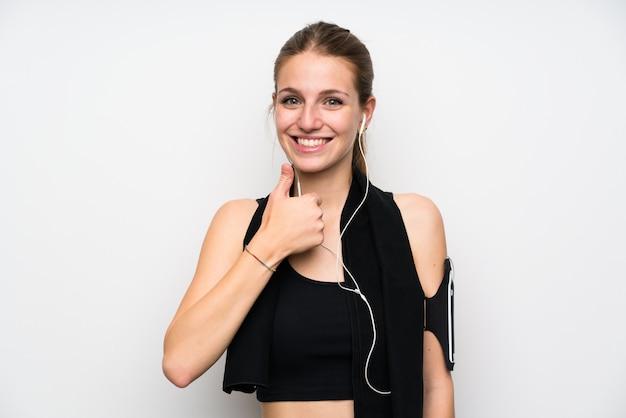 Junge sportfrau über dem lokalisierten weißen wandgeben daumen up geste Premium Fotos