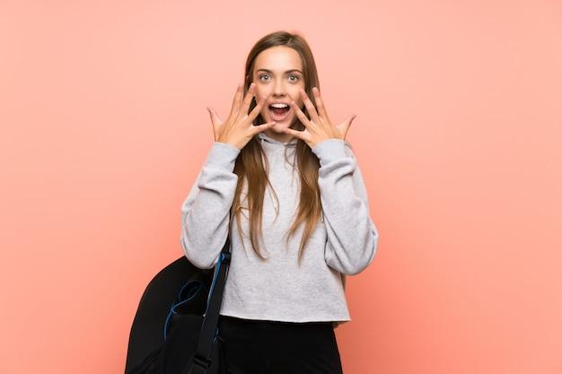 Junge sportfrau über lokalisiertem rosa hintergrund mit überraschungsgesichtsausdruck Premium Fotos