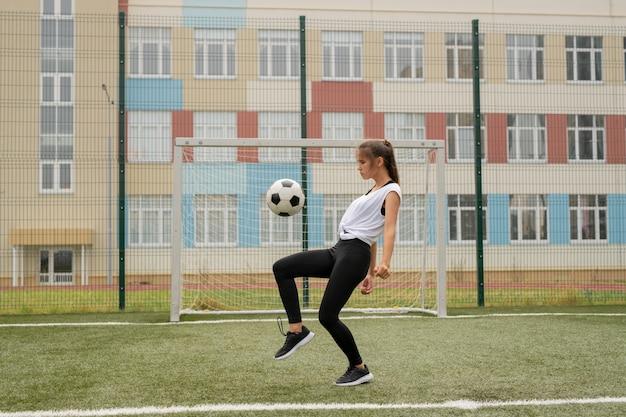 Junge sportlerin in leggins, turnschuhen und t-shirt-training, um fußball zu spielen, während ball auf spielplatz im freien tritt Premium Fotos