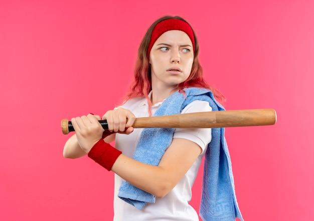 Junge sportliche frau im stirnband mit handtuch auf schulter, die eine fledermaus hält, die beiseite mit ernstem gesicht steht über rosa wand steht Kostenlose Fotos