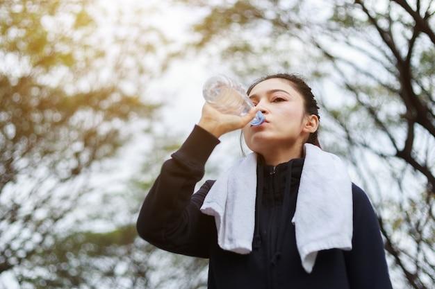 Junge sportliche frau trinkwasser im park Premium Fotos
