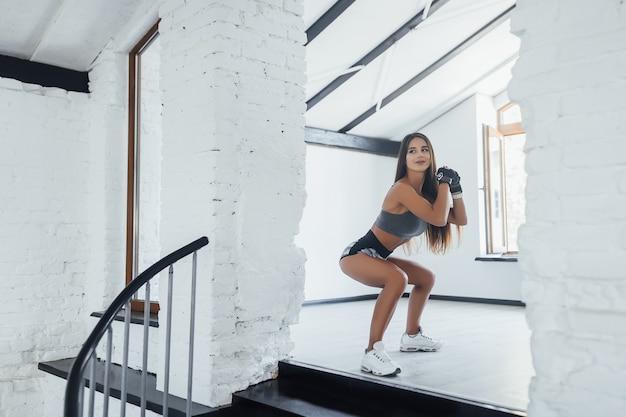 Junge sportliche schönheit, die übungen in der turnhalle tut Premium Fotos