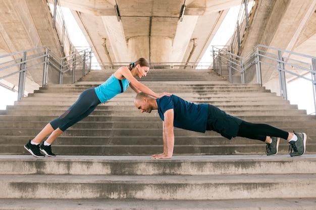 Junge sportpaare, die auf dem treppenhaus trainieren Kostenlose Fotos