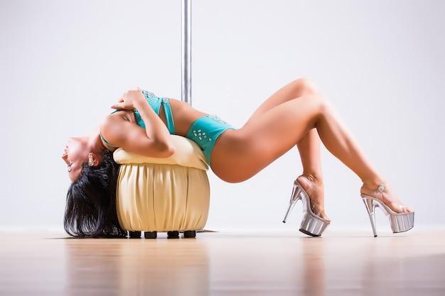 Junge stangentanzfrau, die gymnastik gegen einen weißen hintergrund tut Kostenlose Fotos