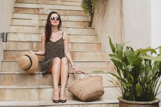 Junge stilvolle attraktive frau im eleganten kleid sitzt auf treppen, strohhut und tasche, sommerstil, modetrend, urlaub, lächeln, stilvolle accessoires, sonnenbrille, posiert auf tropischer villa auf bali Kostenlose Fotos