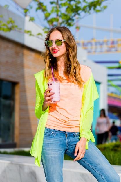 Junge stilvolle blonde hipsterfrau in der kühlen sonnenbrille mit cocktail, der im freien aufwirft Kostenlose Fotos