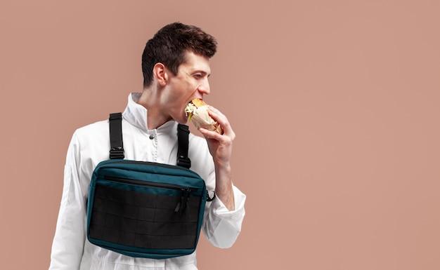 Junge stilvolle männliche arbeitskraft mit kastenplattformbeutel isst einen geschmackvollen saftigen burger auf einem weißen hintergrund Premium Fotos