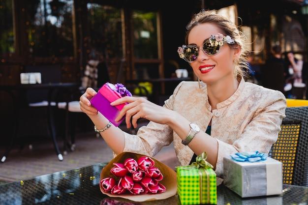 Junge stilvolle schöne frau in der mode-sonnenbrille, die am café sitzt Kostenlose Fotos