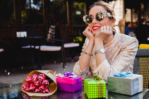 Junge stilvolle schöne frau in der mode-sonnenbrille, die im café mit geschenken sitzt Kostenlose Fotos