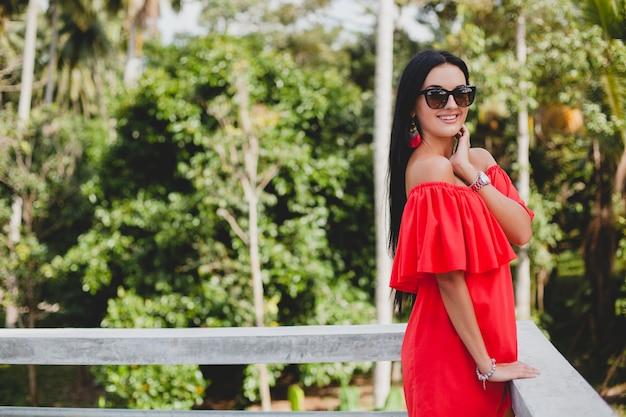 Junge stilvolle sexy frau im roten sommerkleid stehend auf terrasse im tropischen hotel, palmenhintergrund, langes schwarzes haar, sonnenbrille, ethnische ohrringe, sonnenbrille, lächelnd Kostenlose Fotos
