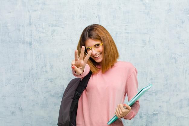 Junge studentenfrau, die freundlich lächelt und schaut, nummer drei oder drittel mit der hand vorwärts zeigt und unten zählt Premium Fotos