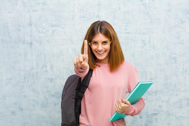 Junge studentenfrau, die freundlich lächelt und schaut, nummer eins oder zuerst mit der hand vorwärts zeigt und unten gegen schmutzwandhintergrund zählt Premium Fotos