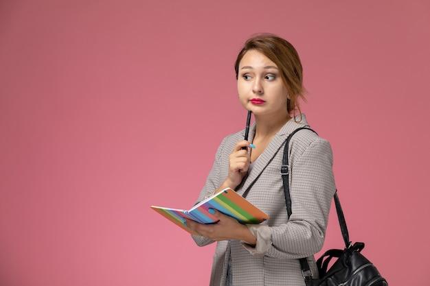 Junge studentin der vorderansicht im grauen mantel, der das heft mit dem denkenden ausdruck auf dem rosa hintergrundunterrichtsuniversitätshochschulstudium aufwirft Kostenlose Fotos