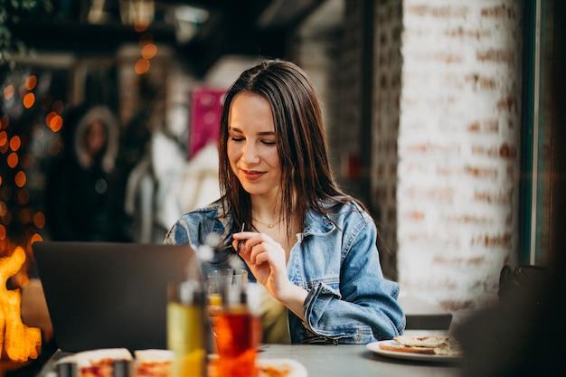 Junge studentin, die an laptop in der bar arbeitet und pizza isst Kostenlose Fotos