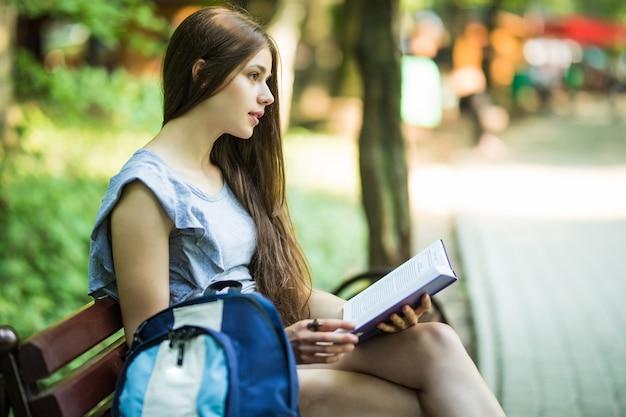Junge studentin, die auf bank sitzt und buch im park liest Kostenlose Fotos
