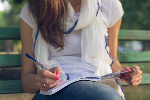 Junge studentin, die auf einer bank im park sitzt Premium Fotos