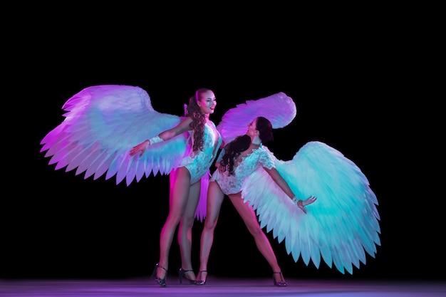 Junge tänzerin mit engelsflügeln im neonlicht auf schwarzer wand Kostenlose Fotos