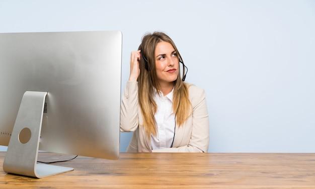 Junge telemarketerfrau, die zweifel und mit verwirrtem gesichtsausdruck hat Premium Fotos