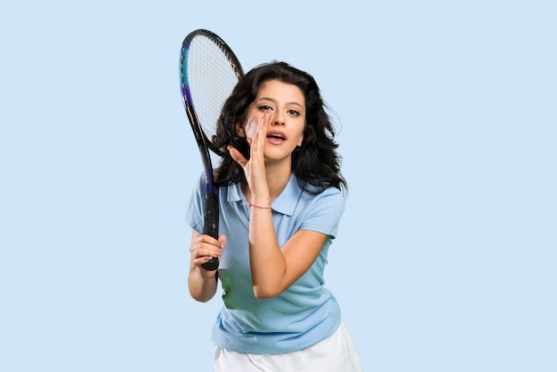 Junge tennisspielerfrau, die etwas flüstert Premium Fotos