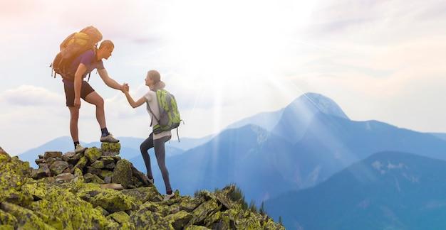 Junge touristen mit rucksäcken, sportlicher junge hilft schlankem mädchen, felsigen berggipfel gegen hellen sommerhimmel und gebirgszug zu klettern. konzept für tourismus, reisen und gesunden lebensstil. Premium Fotos