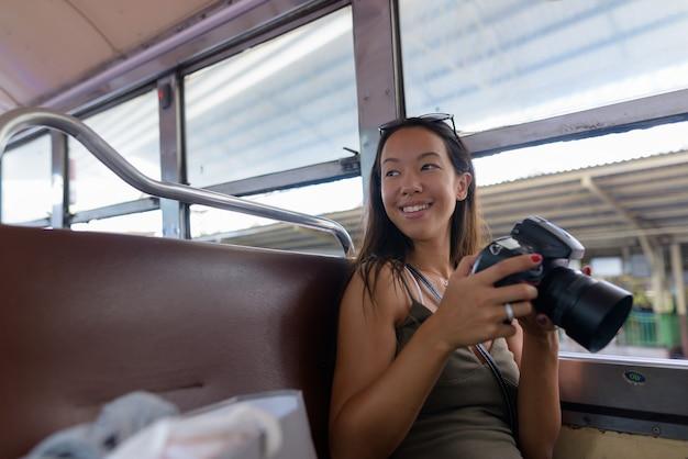 Junge touristenfrau, die am bus sitzt, während dslr-kamera verwendet Premium Fotos