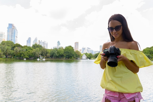 Junge touristenfrau, die kamera in bangkok thailand verwendet Premium Fotos