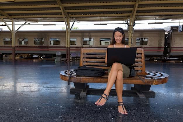 Junge touristenfrau, die laptop-computer sitzt und benutzt Premium Fotos